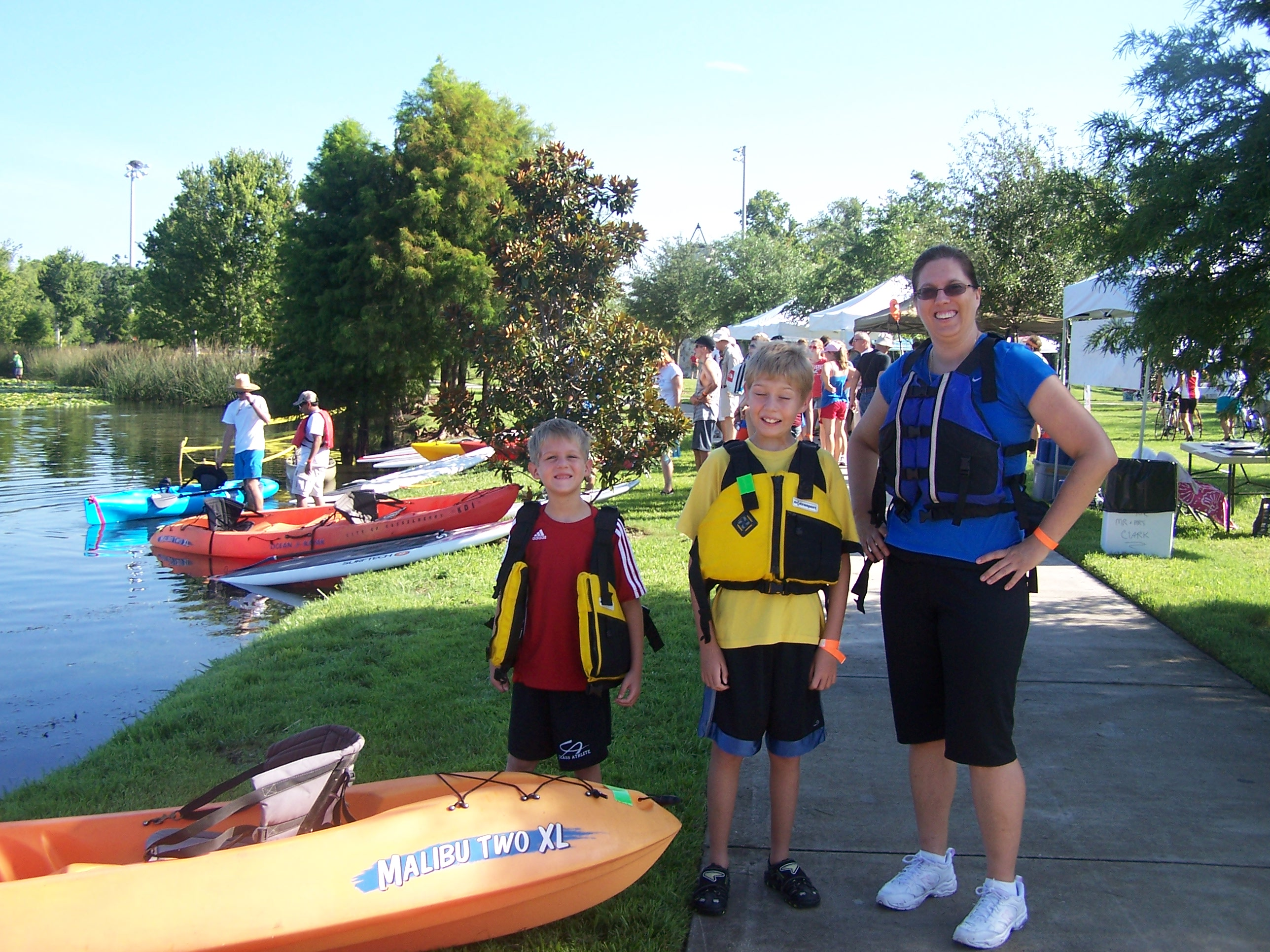 Family wearing life jackets with kayaks